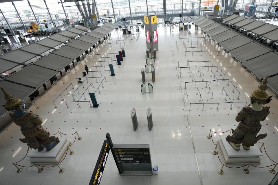 An empty departure terminal is seen at the Suvarnabhumi airport in Bangkok, Thailand, Wednesday, July 21, 2021. The Civil Aviation Authority of Thailand has ordered a halt to all domestic flights operating from the most severely affected provinces effective Wednesday. Exceptions are allowed for flights to destinations that are part of a plan that allows vaccinated travelers from abroad to stay for two weeks on popular islands such as Phuket and Samui without quarantine confinement. (AP Photo/Sakchai Lalit)