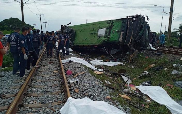 Rescuers stand by a damaged train and bodies covered with sheets after a bus-train collision in Chacheongsao province - Daily News Via AP