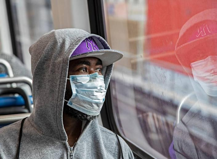 Jim Cantave looks on while riding the Metrorail wearing a protective mask during the COVID19 pandemic in Miami on Wednesday, April 1, 2020.