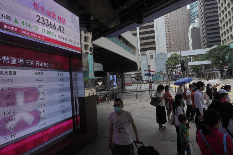 People wearing face masks stand near a bank electronic board showing the Hong Kong share index at Hong Kong Stock Exchange Tuesday, May 26, 2020. Asian shares are rising as some regions in Japan resume near-normal business activity, with hopes for economic recovery overshadowing worries over the coronavirus pandemic. (AP Photo/Vincent Yu)