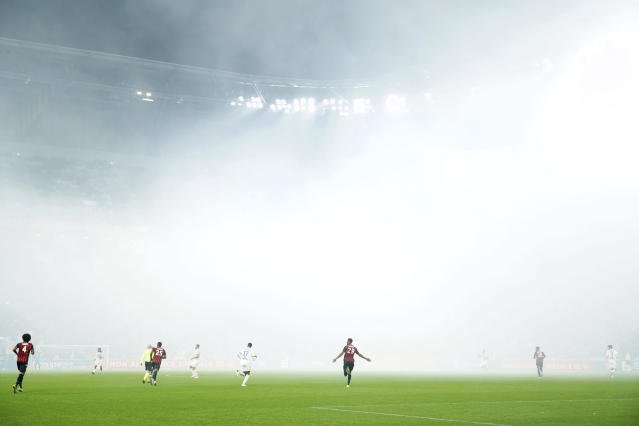 Players of Lyon and Nice are seen in the smoke cover the stadium from flares during the French League One soccer match between Lyon and Nice, at Groupama stadium in Decines, near Lyon, central France, Saturday, Nov. 23, 2019. (AP Photo/Laurent Cipriani)