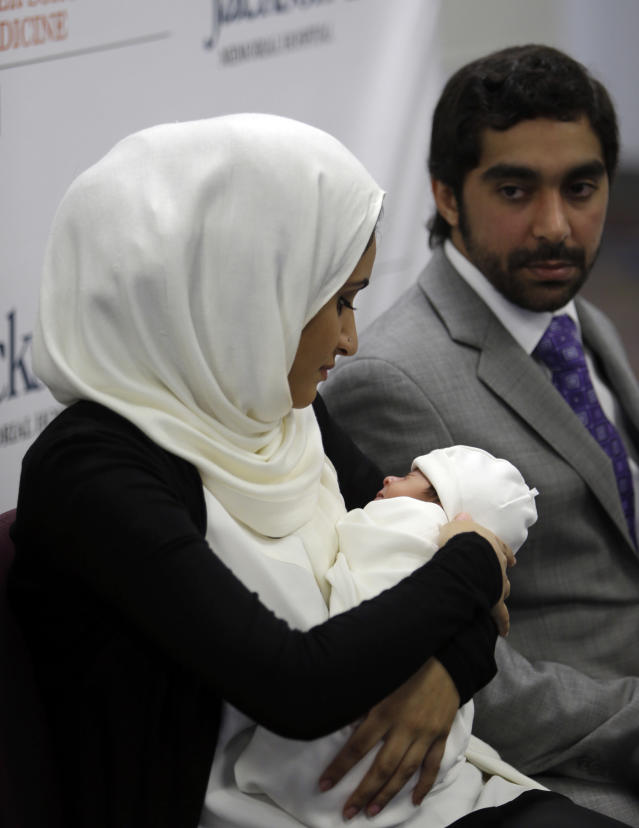 Fatema Al Ansari of Qatar, left, holds her baby Alkadi Alhayal, as her husband Khalifa Alhayal, right, looks on during a news conference at Jackson Memorial Hospital, Wednesday, March 13, 2013, in Miami. Al Ansari was diagnosed with a condition called mesenteric thrombosis at age 19, causing her abdominal organs to fail. She is the first multivisceral transplant patient in the world to conceive and give birth. (AP Photo/Lynne Sladky)