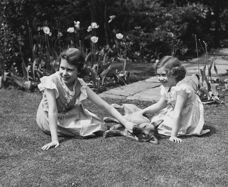 Queen Elizabeth II and Princess Margaret sitting on the grass in the grounds of the Royal Lodge, Windsor, stroking a corgi, 1936.