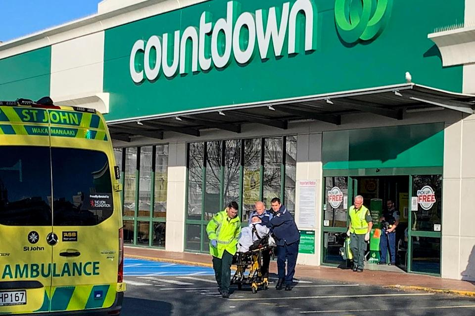 <p>First responders take a victim to an ambulance outside the Countdown supermarket in central Dunedin</p> (AP)