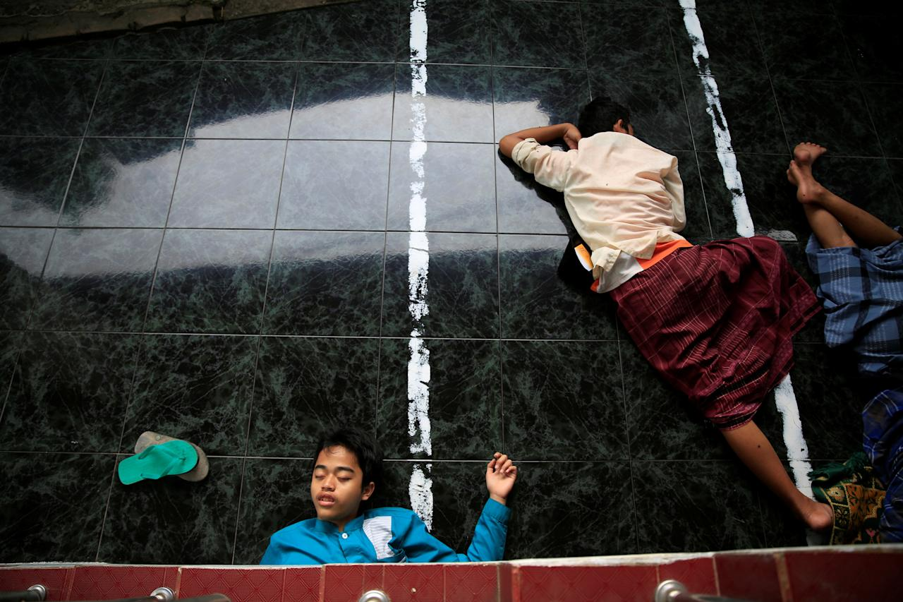 <p>Students sleep at a mosque during the holy month of Ramadan at Lirboyo Islamic boarding school in Kediri, Indonesia, May 16, 2018. (Photo: Beawiharta/Reuters) </p>