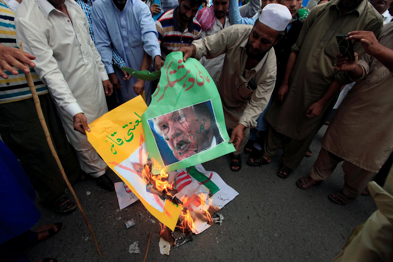 Supporters of religious and political party Jamaat-e-Islami (JI) burn the images of U.S. President Donald Trump and India's Prime Minister Narendra Modi, during a protest against the U.S. decision of putting the leader of an anti-India militant group Syed Salahuddin on its list of global terrorists, in Rawalpindi, Pakistan June 28, 2017. REUTERS/Faisal Mahmood