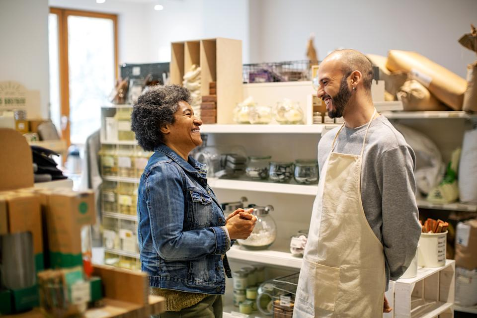 Smiling male owner and female customer laughing while standing at illuminated food zero waste store