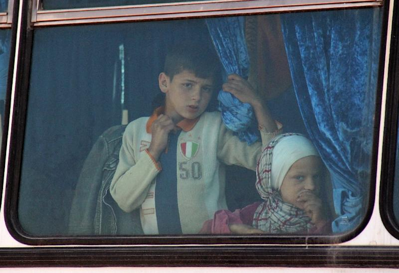 Syrian civilians being evacuated from the government-held towns of Fuaa and Kafraya, which have been under crippling siege for more than two years, on buses near the rebel-held transit point of Rashidin on April 19, 2017 (AFP Photo/Omar haj kadour)