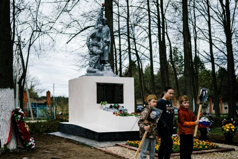 Children hold portraits of relatives who fought in World War II in front of a monument to fallen soldiers in the village of Sokolniki (AFP Photo/Dimitar DILKOFF)