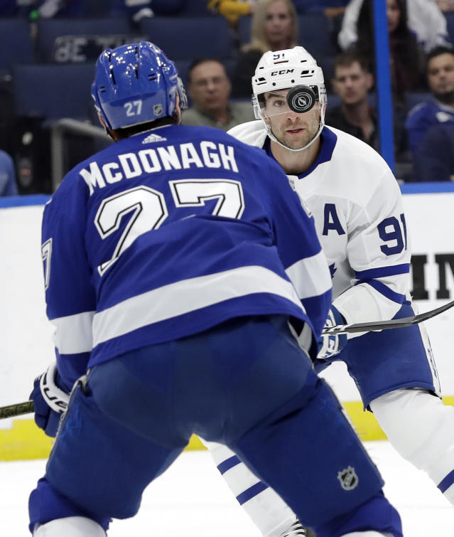 Toronto Maple Leafs center John Tavares (91) eyes a bouncing puck in front of Tampa Bay Lightning defenseman Ryan McDonagh (27) during the first period of an NHL hockey game Thursday, Dec. 13, 2018, in Tampa, Fla. (AP Photo/Chris O'Meara)