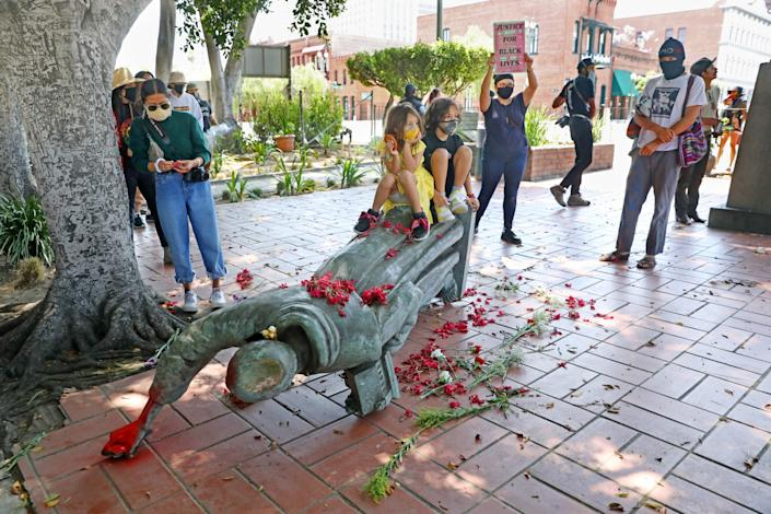 Activists gather near the toppled statue of Father Junipero Serra in Los Angeles' Olvera Street.