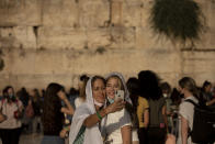 Women pose for a selfie at the Western Wall, the holiest site where Jews can pray, in the shadow of the Mughrabi Bridge, a wooden pedestrian bridge connecting the wall to the Al Aqsa Mosque compound, in Jerusalem's Old City, Tuesday, July 20, 2021. The rickety bridge allowing access to Jerusalem's most sensitive holy site is at risk of collapse, according to experts. But the flashpoint shrine's delicate position at ground-zero of the Israeli-Palestinian conflict has prevented its repair for more than a decade. (AP Photo/Maya Alleruzzo)
