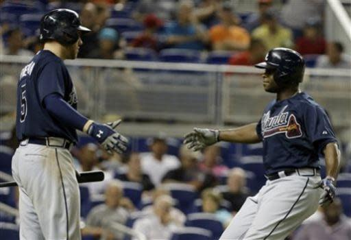 Atlanta Braves' Justin Upton, right, is met by Freddie Freeman, left, after scoring on a solo home run in the eighth inning during a baseball game against the Miami Marlins,Tuesday, July 9, 2013 in Miami. The Braves defeated the Marlins 6-4. (AP Photo/Lynne Sladky)