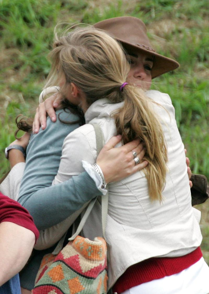 Kate Middleton, then-girlfriend of Prince William, hugs a friend on the second day of the Gatcombe Park Festival on August 6, 2005 near Tetbury, England. (Matt Cardy via Getty Images)