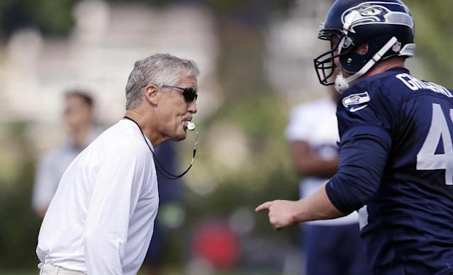 Seattle Seahawks head coach Pete Carroll, left, whistles the play stopped at an NFL football camp practice Friday, July 25, 2014, in Renton, Wash. (AP Photo)