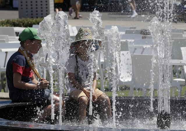 Children cool off in a fountain in Garden Square as temperatures are expected to top 44 C (112 F) during second round matches at the Australian Open tennis championship in Melbourne, Australia, Thursday, Jan. 16, 2014. (AP Photo/Mark Baker)