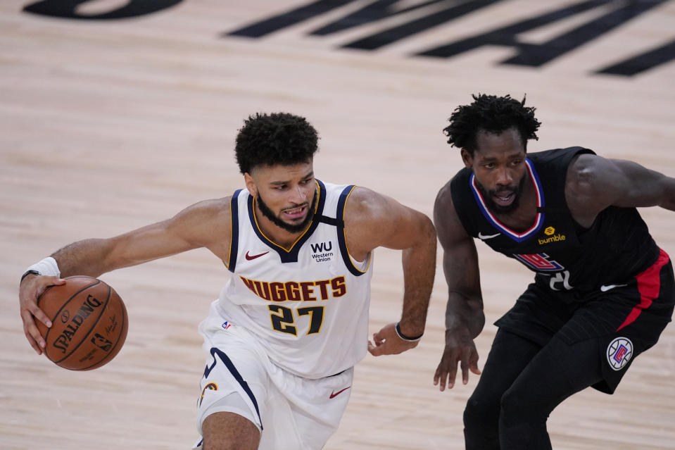 Denver Nuggets guard Jamal Murray (27) drives around LA Clippers guard Patrick Beverley (21) during the first half of an NBA conference semifinal playoff basketball game Tuesday, Sept. 15, 2020, in Lake Buena Vista, Fla. (AP Photo/Mark J. Terrill)