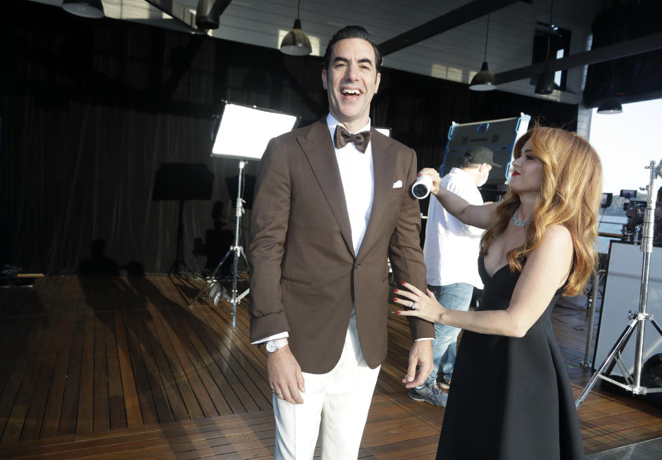 Isla Fisher helps make the final touches to clean the suit of Sacha Baron Cohen as they arrive to attend a screening of the Oscars on Monday April 26, 2021 in Sydney, Australia. (AP Photo/Rick Rycroft, Pool)