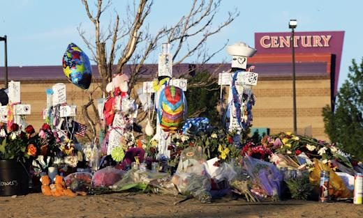 Crosses, flowers and other mementos of the victims of the Aurora, Colo., movie theater shooting are shown at sunrise a week after the tragedy. (AP/Ted S. Warren)