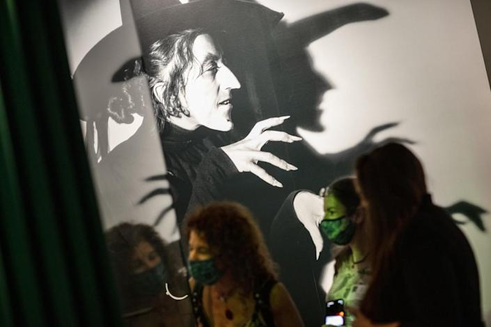 Visitors stand in front of a large photo of a witch.