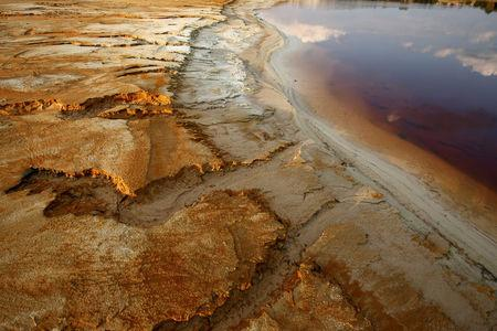 FILE PHOTO - Polluted water emanating from mining operations fills a dam near Johannesburg