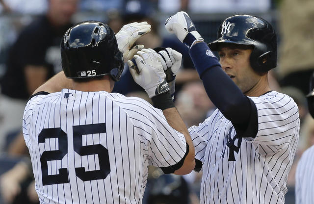 New York Yankees' Derek Jeter, right, congratulates Mark Teixeira (25) after Teixeira hit a two-run home run against the Pittsburgh Pirates during the first inning of a baseball game, Saturday, May 17, 2014, in New York. Jeter scored on the homer. (AP Photo/Julie Jacobson)