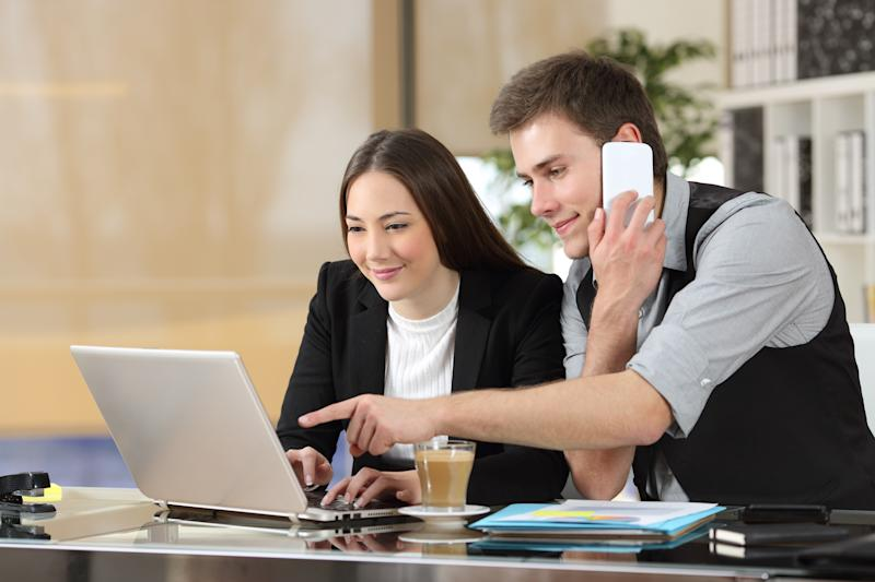 Two young office workers sharing a laptop while one points to the screen while talking on a smartphone.