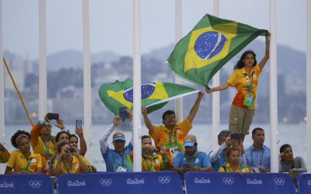 2016 Rio Olympics - Sailing - Victory Ceremony - Women's Skiff - 49er FX - Victory Ceremony - Marina de Gloria - Rio de Janeiro, Brazil - 18/08/2016. Volunteers raise Brazilian flag during national anthem. REUTERS/Brian Snyder FOR EDITORIAL USE ONLY. NOT FOR SALE FOR MARKETING OR ADVERTISING CAMPAIGNS.