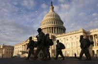National Guard members walk in front of the U.S. Capitol after the House voted to impeach U.S. President Donald Trump in Washington