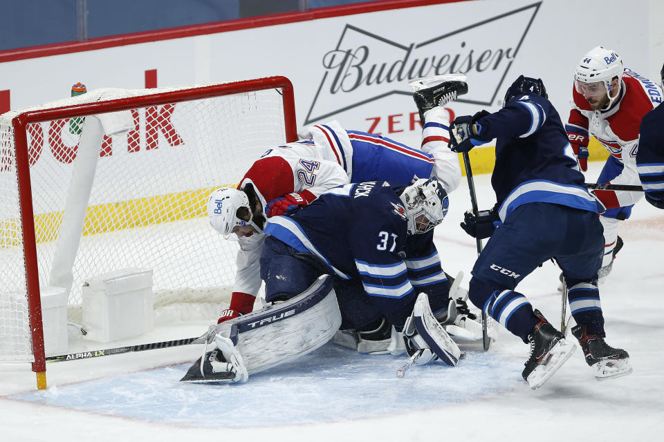 Winnipeg Jets goaltender Connor Hellebuyck (37) makes a save as Montreal Canadiens' Phillip Danault (24) crashes into him during the second period of an NHL hockey game Saturday, Feb. 27, 2021, in Winnipeg, Manitoba. (John Woods/The Canadian Press via AP)