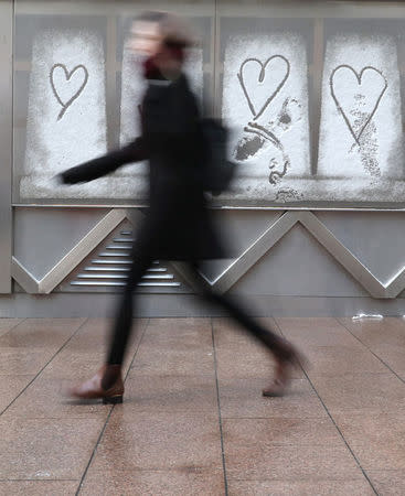 A woman walks past hearts that have been drawn in the snow, in Canary Wharf financial district, London, Britain February 28, 2018. REUTERS/Russell Boyce