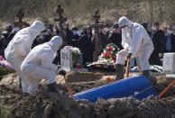 Grave diggers wearing protective suits bury a COVID-19 victim as relatives and friends stand at a safe distance, in the special purpose for coronavirus victims section of a cemetery in Kolpino, outside St.Petersburg, Russia, Sunday, May 10, 2020. (AP Photo/Dmitri Lovetsky)