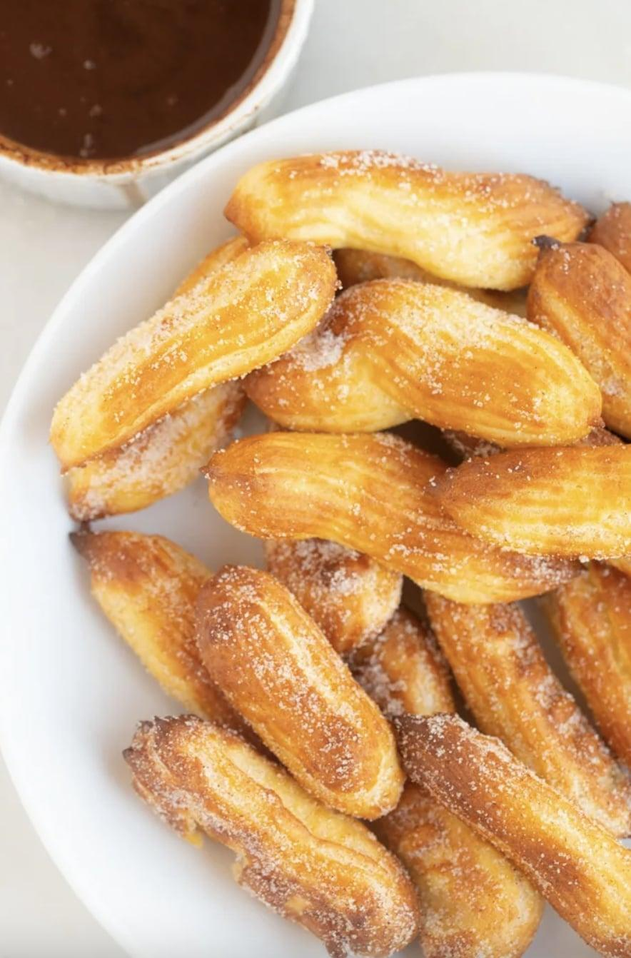 """<p>Light, fluffy, and melt-in-your-mouth good, this homemade churro recipe will blow you away with how easy they are to make. Once you mix all the ingredients together, just throw them into the air fryer, and your work is done! Serve them with a warm chocolate sauce for best results.</p> <p><strong>Get the recipe</strong>: <a href=""""https://www.myforkinglife.com/homemade-churros-air-fryer-or-stovetop/"""" class=""""link rapid-noclick-resp"""" rel=""""nofollow noopener"""" target=""""_blank"""" data-ylk=""""slk:air fryer churros"""">air fryer churros</a></p>"""