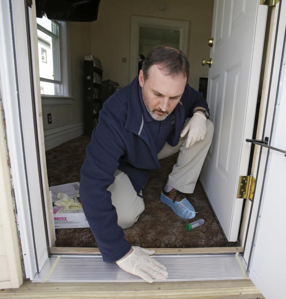 Cuyahoga County Board of Health lead risk assessor Tom Barsa swipes a doorway for lead Thursday, April 4, 2013, in Lakewood, Ohio. More than half a million U.S. children are now believed to have lead poisoning, roughly twice the previous high estimate, health officials reported Thursday. The increase is the result of the government last year lowering the threshold for lead poisoning, so now more children are considered at risk. (AP Photo/Tony Dejak)