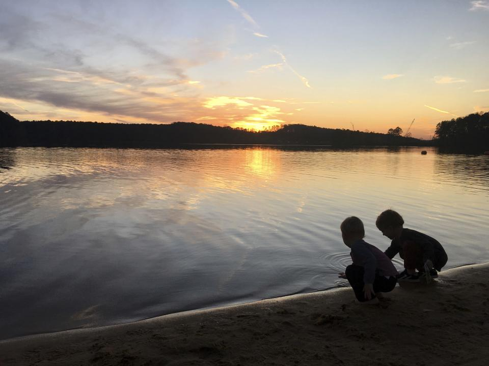 This image provided by Lucy O'Donoghue shows a children playing by a lake. Although this year's quarantine limited Lucy O'Donoghue's opportunities for travel, she found ways to focus on her two sons by taking them for 'micro-holidays' at a beach near their Georgia home. (Lucy O'Donoghue via AP)