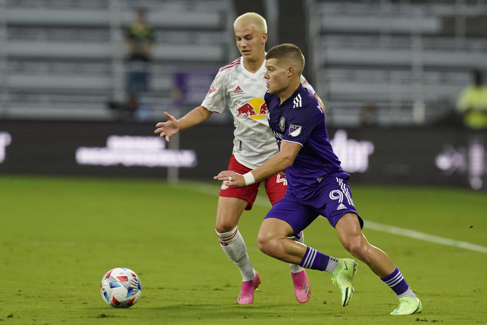 Orlando City forward Chris Mueller (9) moves the ball past New York Red Bulls defender John Tolkin during the first half of an MLS soccer match Saturday, July 3, 2021, in Orlando, Fla. (AP Photo/John Raoux)