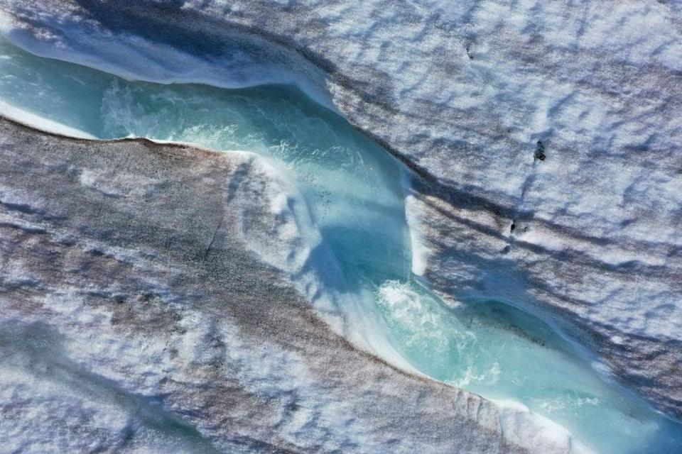 Water carves a winding channel down the surface of the melting Longyearbyen glacier during a summer heat wave on Svalbard archipelago in 2020, approximately 1,200km north of the Arctic Circle (Getty Images)