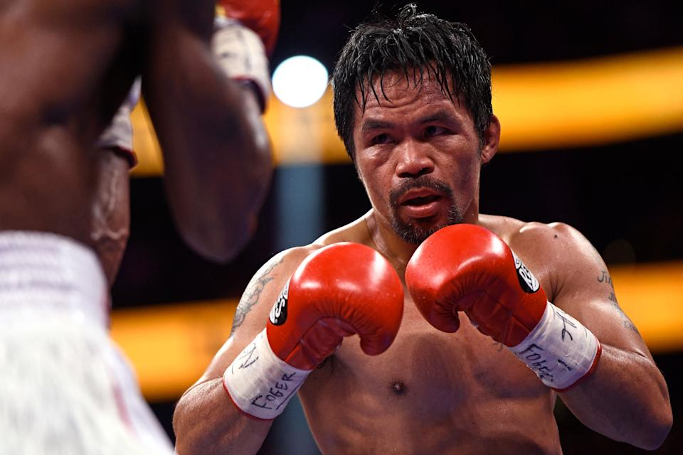 Manny Pacquiao (R) of the Philippines fights against Yordenis Ugas of Cuba during the WBA Welterweight Championship boxing match at T-Mobile Arena in Las Vegas, Nevada on August 21, 2021. - Cuba's Yordenis Ugas upset Manny Pacquiao to retain his WBA welterweight crown on Saturday, winning by unanimous decision after a bruising 12-round battle at the T-Mobile Arena. (Photo by Patrick T. FALLON / AFP) (Photo by PATRICK T. FALLON/AFP via Getty Images)