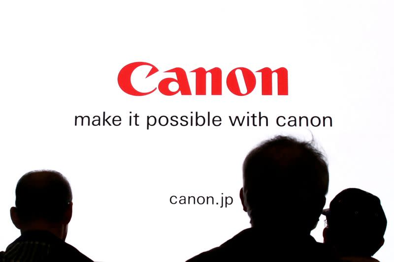 People are silhouetted against a display of the Canon brand logo at the CP+ camera and photo trade fair in Yokohama, Japan