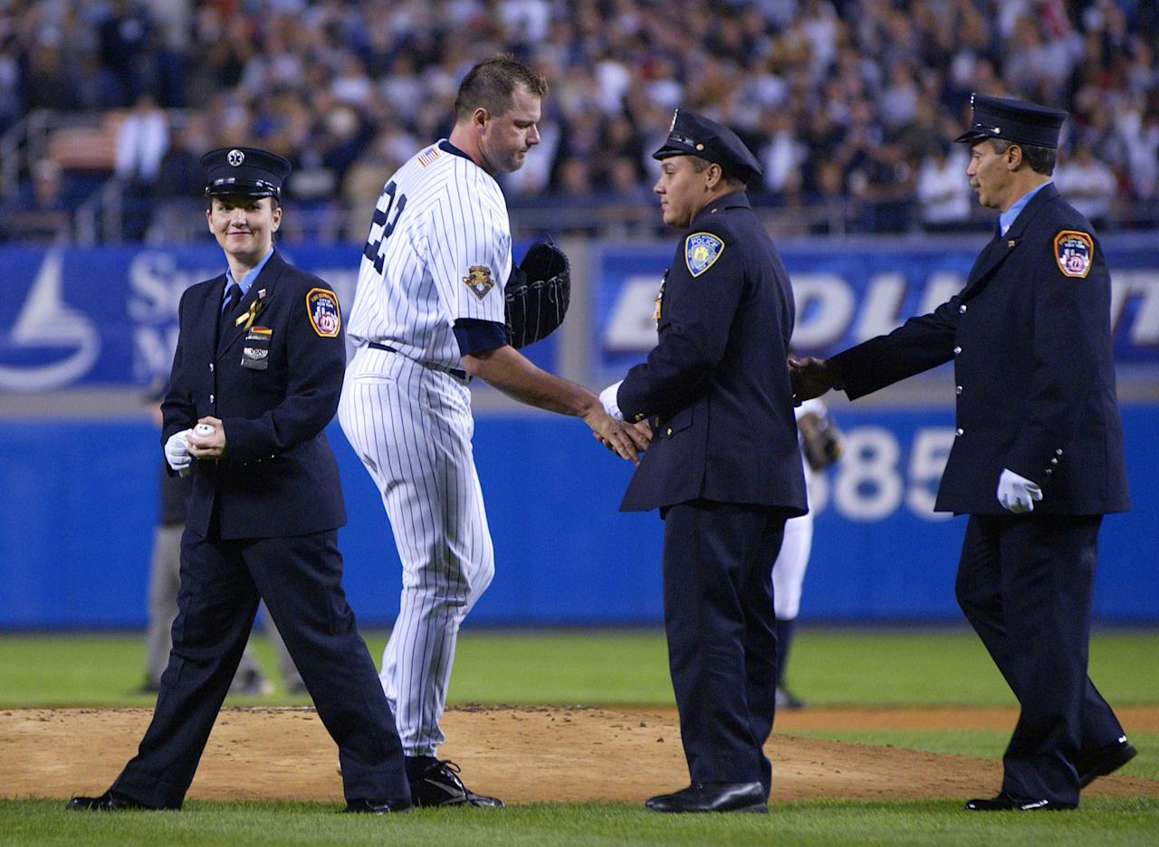 Roger Clemens of the New York Yankees shakes hands with World Trade Center disaster rescue workers, one of who threw out the first pitch, before a game against the Tampa Bay Devil Rays at Yankee Stadium September 25, 2001 in the Bronx, New York. Tonight's game is the first played at Yankee stadium since the terrorist attack on the twin towers. (Photo by Ezra Shaw/Allsport/Getty Images)