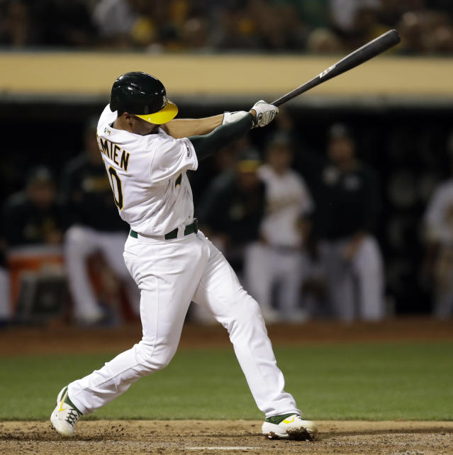 Oakland Athletics' Marcus Semien swings for a two-run double off Texas Rangers' Lance Lynn in the fourth inning of a baseball game, Tuesday, April 23, 2019, in Oakland, Calif. (AP Photo/Ben Margot)