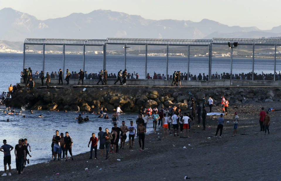 People from Morocco swim and walk into the Spanish territory at the border of Morocco and Spain, at the Spanish enclave of Ceuta on Monday, May 17, 2021. Authorities in Spain say that around 1,000 Moroccan migrants have crossed into Spanish territory (Antonio Sempere/Europa Press via AP)