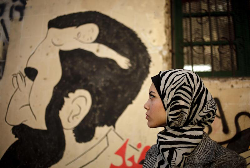 "FILE - In this Tuesday, Dec. 10, 2013 file photo, Egyptian rapper Myam Mahmoud poses for a portrait next to a mural in downtown Cairo. Mahmoud, an 18-year-old Egyptian, rapped her way to the semi-finals of the Middle East's hit TV show ""Arabs Got Talent."" While she didn't win the program, Mahmoud did succeed in throwing a spotlight on something more than just herself. On a very public stage, her songs pulled back the curtain on the slew of challenges that women across the Arab world are fighting to overcome. (AP Photo/Maya Alleruzzo, File)"