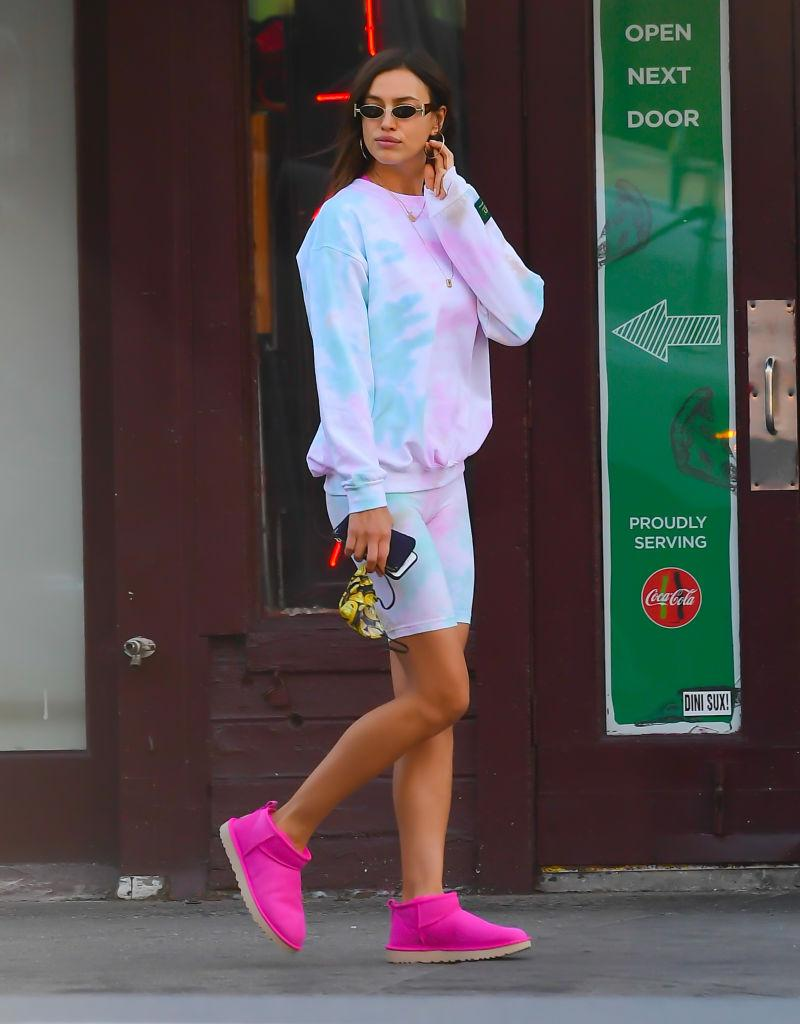 """The supermodel opted for a pair of hot pink Uggs for a stroll through New York City. <em>(Image via Getty Images)</em> <em><strong>SHOP IT: </strong></em><a href=""""https://fave.co/3sW0gmt"""" rel=""""nofollow noopener"""" target=""""_blank"""" data-ylk=""""slk:Ugg, $140 USD"""" class=""""link rapid-noclick-resp""""><em><strong>Ugg, $140 USD</strong></em></a>"""