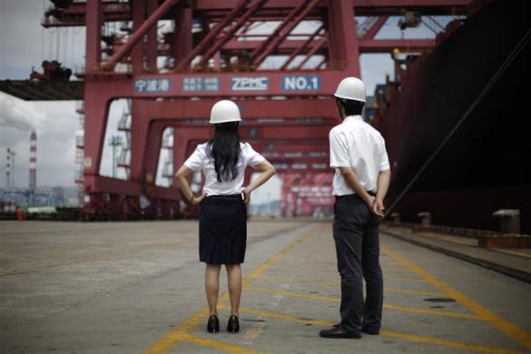 Employees stand next to a container ship at Ningbo port in Ningbo, Zhejiang province June 21, 2012.