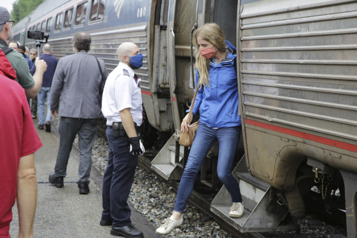 A passenger, right, gets off the Amtrak Vermonter passenger train after it arrived at the Montpelier station, in Berlin, Vt., Monday July 19, 2021. Celebrations were held at Amtrak stations across the state to mark the return of the passenger trains to Vermont for the first time since they were suspended at the beginning of the COVID-19 pandemic. (AP Photo/Wilson Ring)