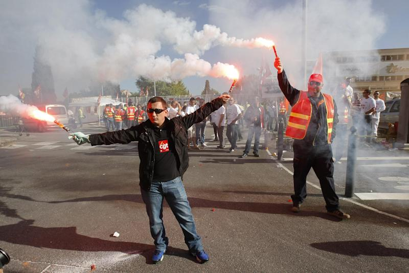 Employees of Arkema Kem One chemical company and employees of other petrochemical sites, burn  flares as they block the Arkema plant in Marseille, southern France, Tuesday, May 14 , 2013. Kem One, the maker of vinyl products  announced last July it may cuts jobs. (AP Photo/Claude Paris)