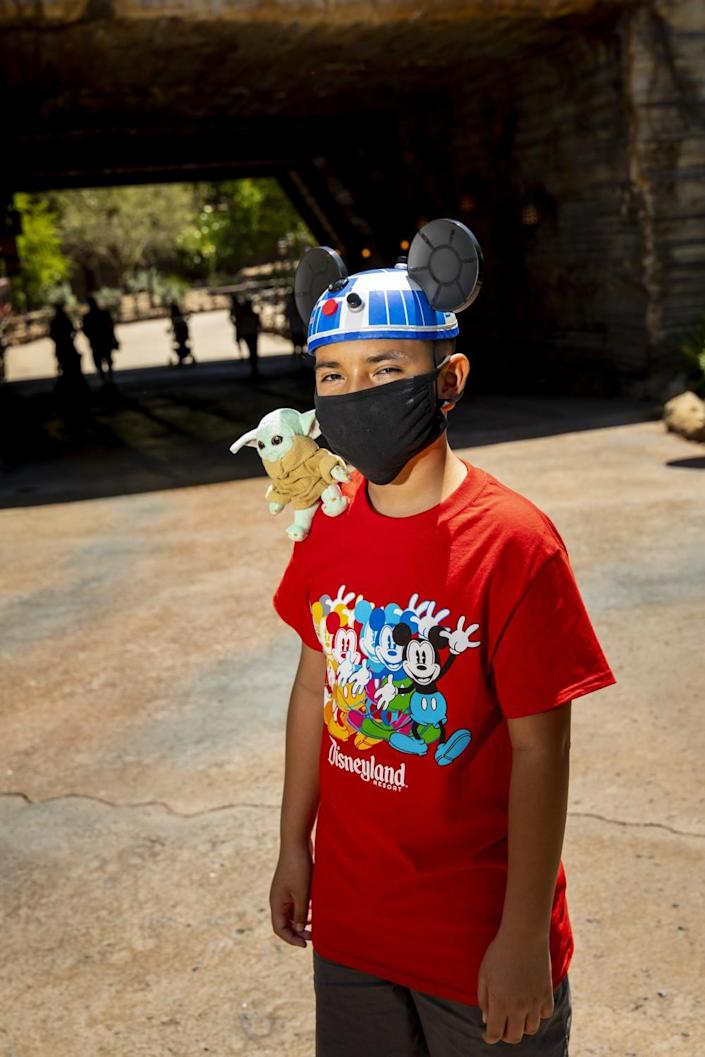 A boy in a Disneyland shirt and R2-D2 hat has a baby Yoda on his shoulder