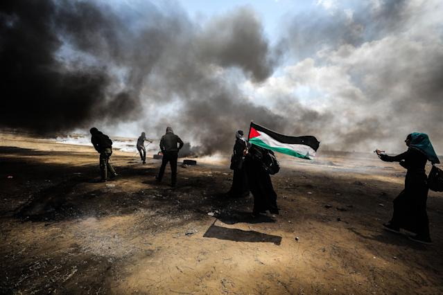 <p>Palestinians set tires on fire in response to Israel's intervention during a protest organized to mark 70th anniversary of Nakba, also known as Day of the Catastrophe in 1948, and against the United States' relocation of its embassy from Tel Aviv to Jerusalem, near the Gaza-Israel border in Khan Younis on May 14, 2018. (Photo: Mustafa Hassona/Anadolu Agency/Getty Images) </p>
