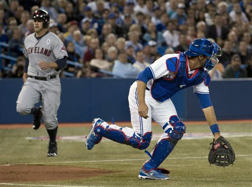 Toronto Blue Jays catcher J.P. Arencibia waits for the throw as Cleveland Indians designated hitter Mark Reynolds, left, runs in to score during the second inning of an opening day baseball game in Toronto on Tuesday, April 2, 2013. (AP Photo/The Canadian Press, Nathan Denette)